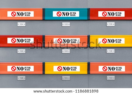 Multicolored modern mailboxes with no junk mail stickers on every box. Front view illustrative picture #1186881898