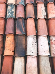 Multicolored old roof tiles in orange, red, pink, and gray colors. Abstract background pattern of rooftop textured color