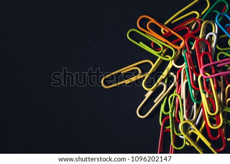 Multicolored paper clips on a dark background