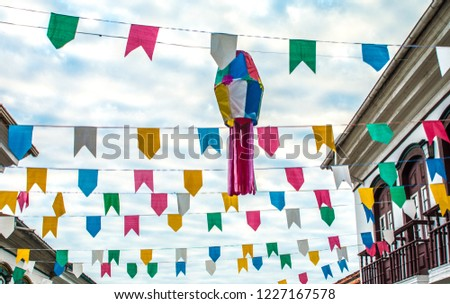 Multicolored paper flags and balloons against cloud blue sky in brazilian june party (also