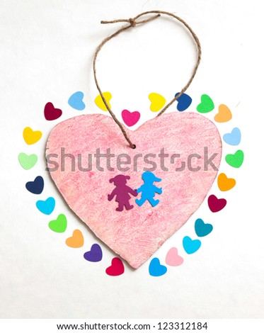 multicolored paper hearths with  a wooden pink heart and paper boy and girl  on white paper