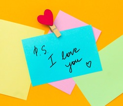 multicolored paper notes with text ps i love you  with cloth pin decorated with red heart   on a vibrant yellow background