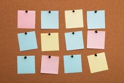 Multicolored paper stickers on cork board