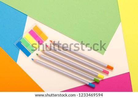 multicolored pencils and multicolored paper, top view #1233469594