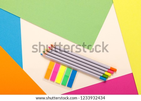 multicolored pencils and multicolored paper, top view #1233932434