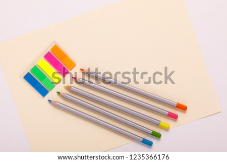 multicolored pencils and multicolored paper, top view #1235366176
