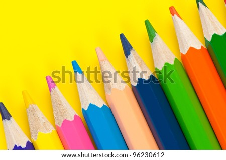 Multicolored pencils close up on a bright yellow background