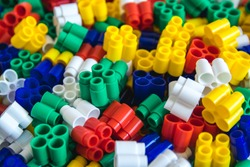 Multicolored plastic building blocks of the designer. Background of plastic colored details building blocks. Parts of bright small spare parts for toys. Close up.