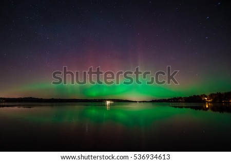 Multicolored red and green Aurora Borealis (Northern Lights) reflected over calm water surface. Stockholm, Sweden. #536934613