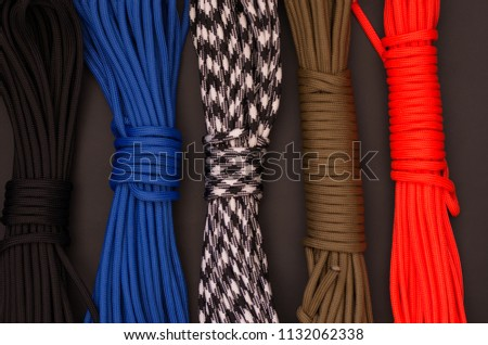 Multicolored ropes. Multicolored paracord. Various convolutions of threads. #1132062338