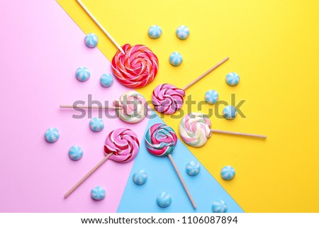 Multicolored round candy and colored lollipops on colored bright backgrounds. Top view