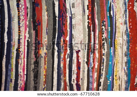 Multicolored rug, made of different pieces. Frontally, a fragment, closeup.