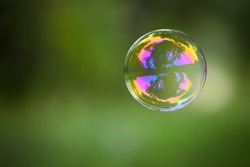 multicolored soap bubble on a green background. Soap bubble. Isolated on green, in spring or summer. reflex, detailed, close-up. multi-colored ball flies. holiday concept, childhood