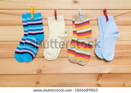 Photo of  multicolored socks hanging on a clothesline with clothespins on a wooden background