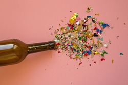 Multicolored sparkling candy on a pink background.Candy spills out of the wine bottle.. Bottle from wine and candy on a pink background