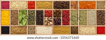 Multicolored spices in a wooden organizer, top view. Seasoning background