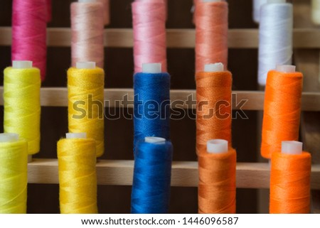 Multicolored spools of thread organized on a wooden stand  #1446096587