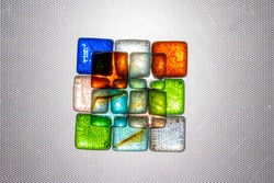 Multicolored square pieces of glass are illuminated through a textured background