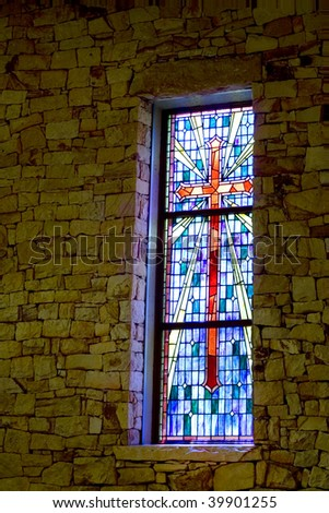 Multicolored stained glass pattern with cross motif in a stone clad wall