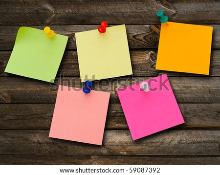 Multicolored stickers and notes and drawing pins at the wooden background - stock photo