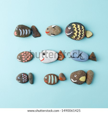 Multicolored stones and creative fish made of stone. The painting is painted in different colors in texture style on blue, DIY, kindergarten, daycare creative art, hobby
