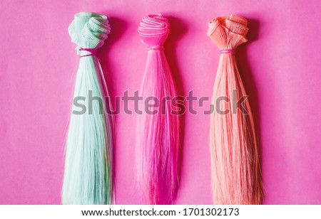 Multicolored straight long hair, wigs for handmade dolls on pink background. Handwork, hobby, leisure concept. Top view. Colored strands of hair. ストックフォト ©