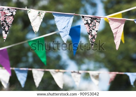 Multicolored summer Bunting flags hanging at an English garden party fete.