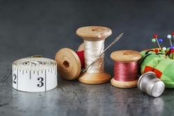 Multicolored threads on a wooden spool, sewing needle with scissors thimble and tailor's tape on an old surface. Sewing thread background. Retro style. Selective focus