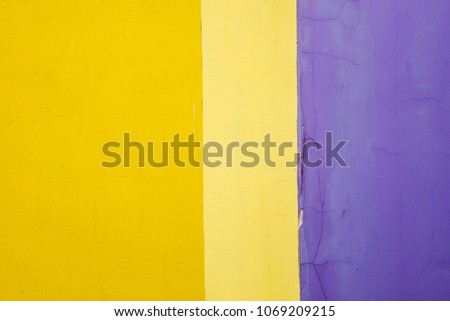 Multicolored wall with cracks. The wall consists of three colors - bright yellow, pale yellow and purple. Can be used as a background. #1069209215