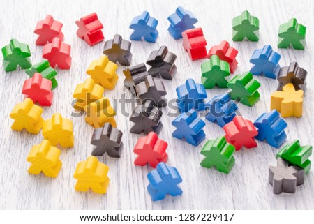 Multicolored wooden figures in the form of stars. Parts of the board game. Leadership skills. The development of logic. Number one, winner and loser. Back and front background in blur. #1287229417