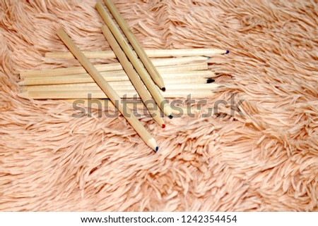 Multicolored wooden pencils on a fluffy bedspread #1242354454
