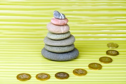 Multicolored zen stones and coins on a wavy surface