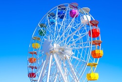 Multicolour ferris wheel on blue sky background