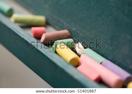 Multicoloured chalk and a chalkboard at a classroom