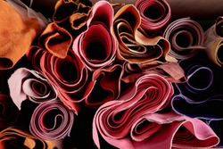 Multicoloured leather in rolls on the shelf in a shop for hand crafting or hand made. Natural material, ecological