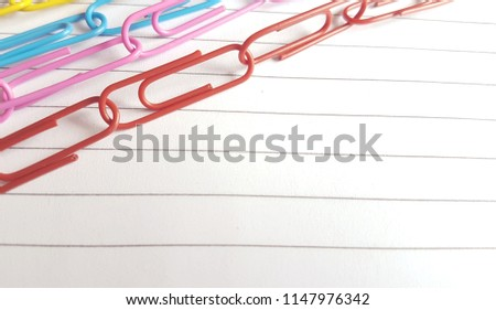 multicoloured paperclips on lined white paper