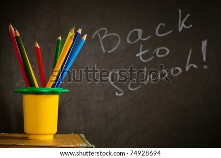 Multicoloured pencil in holder against blackboard with text