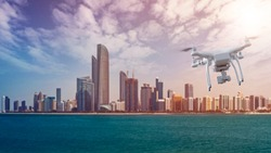 multicopter drone flying in front over the Skyline of Abu Dhabi, capital of the United Arab Emirates with around 1 million inhabitants