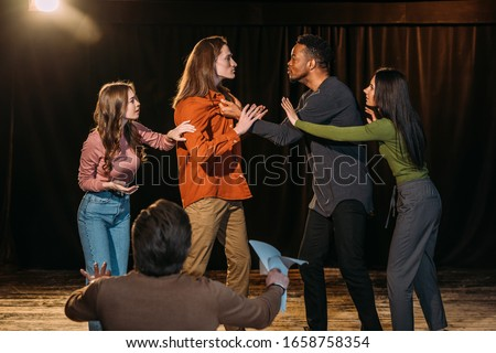multicultural actors and actresses rehearsing fight on stage in theatre Сток-фото ©