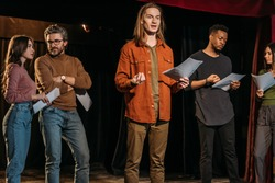 multicultural actors and actresses rehearsing with scripts on stage in theatre