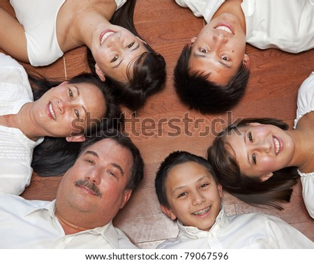 multicultural American family photographed from above laying in a ring.