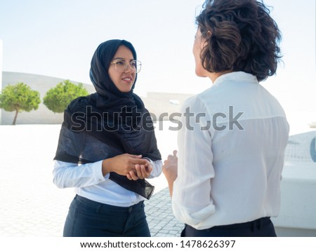 Multicultural businesswomen meeting outside. Caucasian and Muslim business partners standing on square and talking. Businesswoman in hijab concept #1478626397