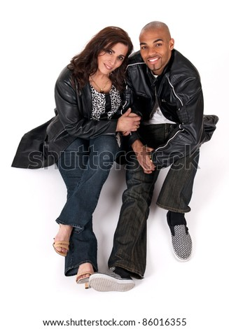 Multicultural couple. Mature woman holding the arm of her younger boyfriend.