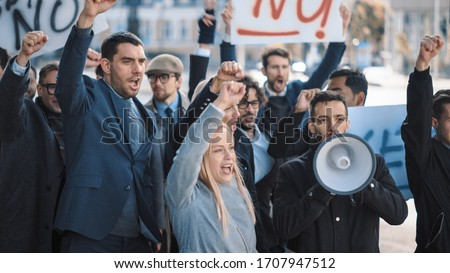 Multicultural Diverse Office Managers and Business People Picketing Outside on a Street. Men and Women Screaming for Justice, Holding a Megaphone, Picket Signs and Posters. Economic Crisis Strike. Foto stock ©