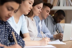 Multicultural diverse students sit at shared desk making notes studying together at university, multiethnic mixed school group write listen to tutor teacher talk giving lecture at college or school
