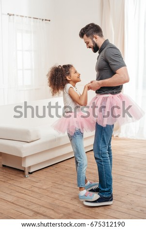 multicultural  father and daughter in pink tutu tulle skirts dancing together #675312190