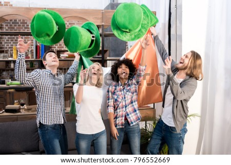 multicultural friends throwing up green hats on patricks day