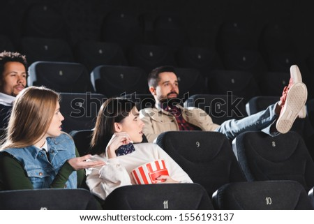 multicultural friends with popcorn looking at ill-mannered man in cinema  Foto stock ©