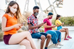 Multicultural friends with surgical mask using tracking app on mobile smart phones - Bored young milenial people at ferris wheel - New normal lifestyle and social distancing concept - Vivid filter