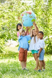 Multicultural group of children together holds up a world globe
